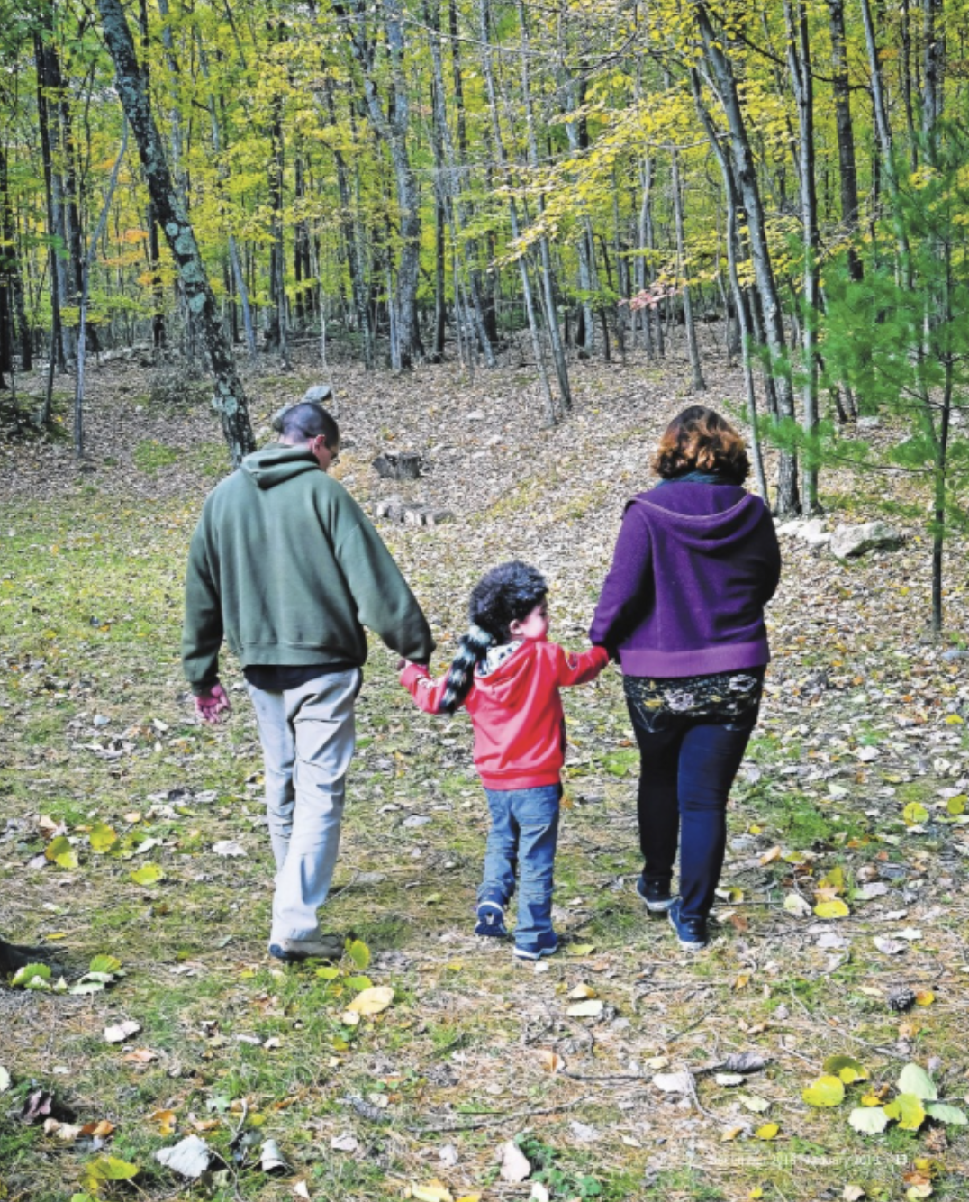 At right, Erica Tortorella, son RJ Sanders and husband Raymond Sanders walk in the backyard of their home in Pine Bush. [PHOTO BY JOHN DESANTO]